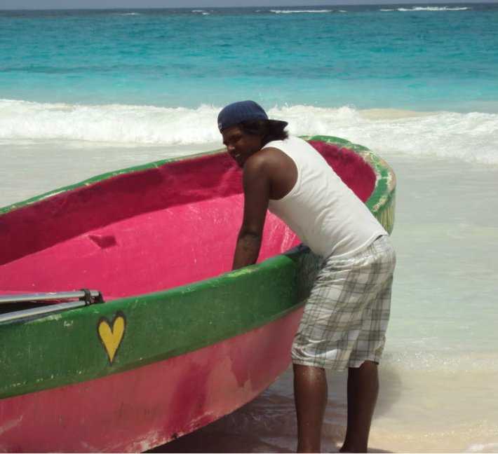 Man with pink boat in Tulum, Mexico.