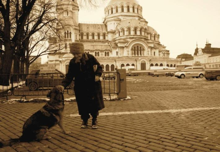 An old woman patting her dog outside the Alexander Nevsky Cathedral in Sofia Bulgaria