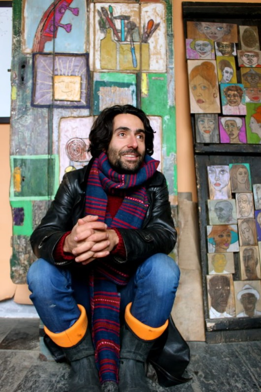 Man sitting in front of colourful art. Dragan Milev's gallery Sofia Bulgaria.