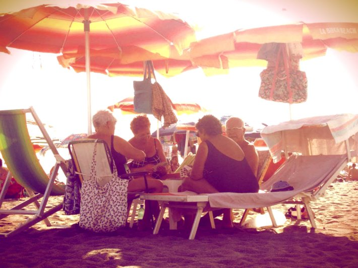 Old people playing cards on the beach. Fiumicino, Italy.