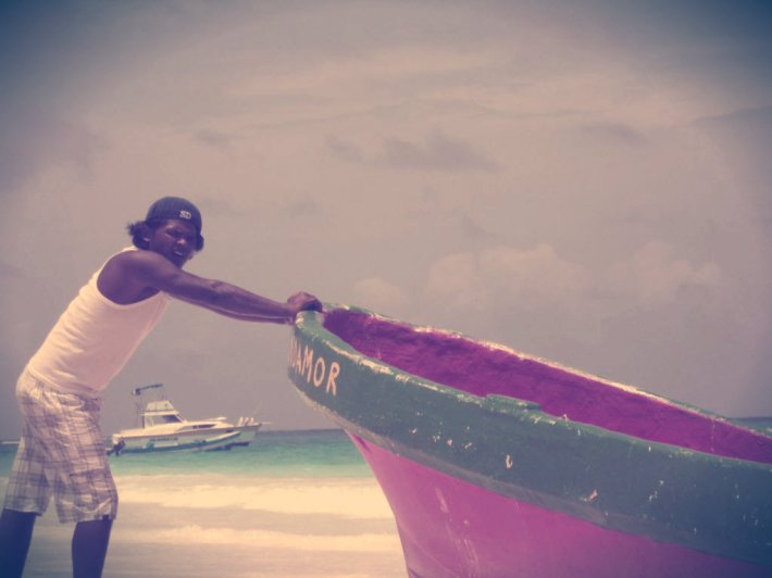 Man pushing pink boat. Tulum, Mexico.