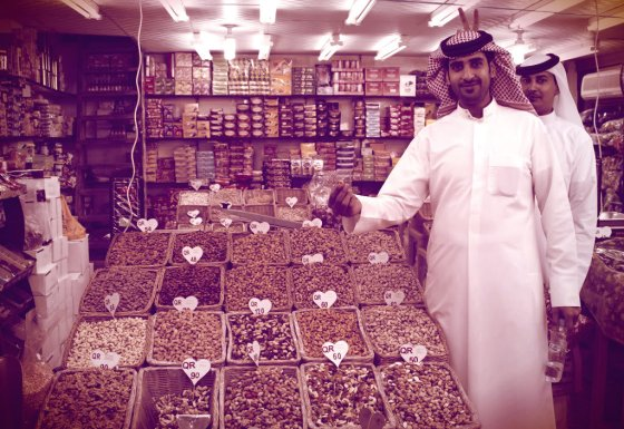 Two men buying nuts in a shop. Doha, Qatar.