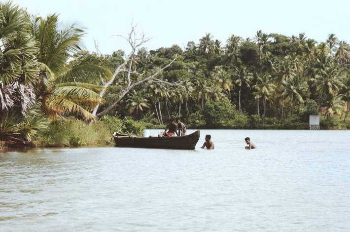 Boys fishing for Yabbies in the backwaters of Kerala with a small wooden boat